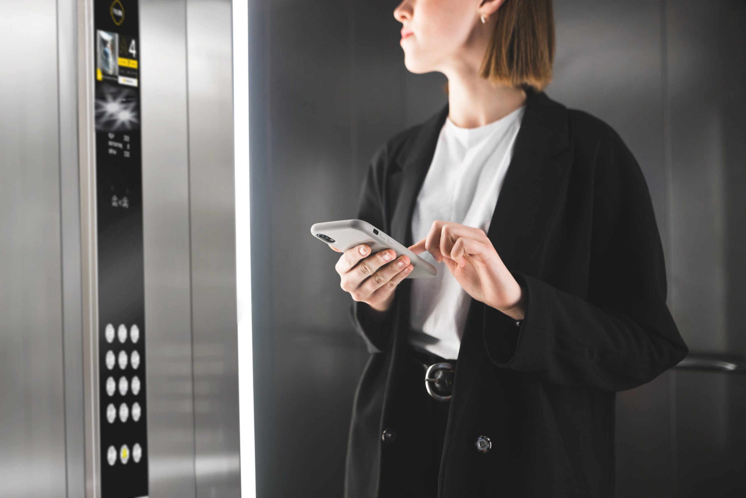 Young employee is looking at the floor number in the elevator holding smartphone. Smart businesswoman is keeping the cellphone in her hands in the lift.